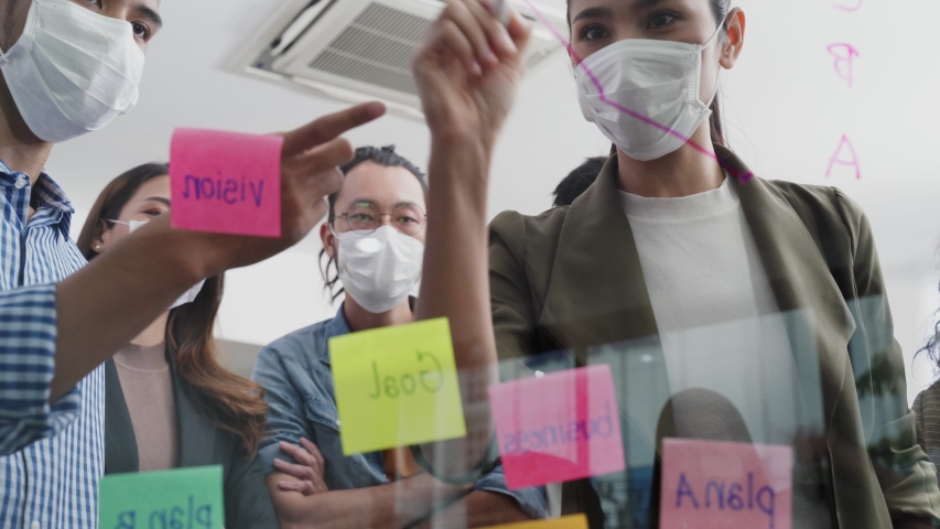 Group brainstorming of Asian people putting sticky note, put it on window. Teamwork business people wearing mask prevent covid infection having discussion and share an idea to solve problem in office. Royalty-Free Stock Footage #1057536991