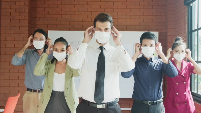 Group of young businesspeople works in meeting room in office with new normal lifestyle. People wearing protective face mask to prevent covid infection. Man and woman put on mask and smile at camera. Royalty-Free Stock Footage #1057537474