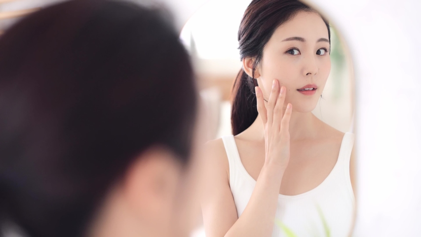 Beautiful asian woman looking at a mirror. Royalty-Free Stock Footage #1057541158