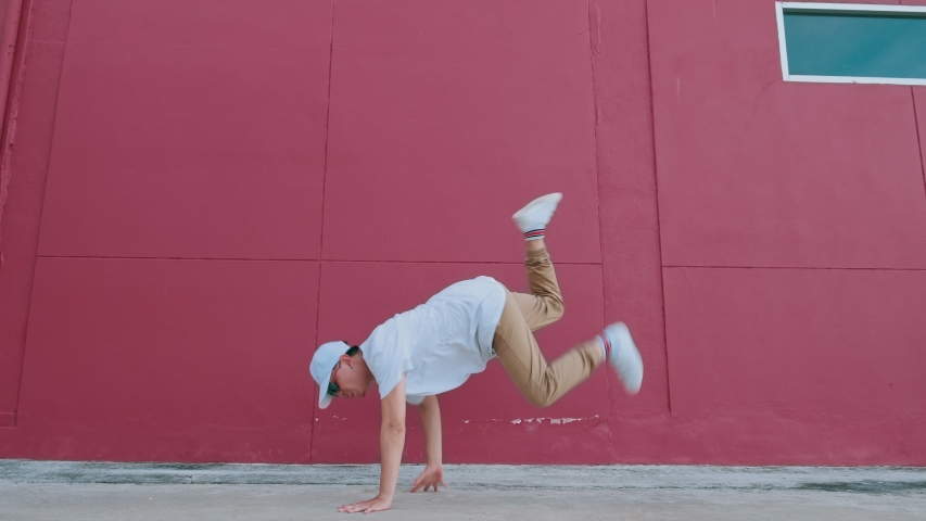 Dancing man performing various freestyle dance outdoors in street wall having fun. Modern lifestyle, happiness concept. breakdancing, hiphop dancing, street dancing. | Shutterstock HD Video #1057542556