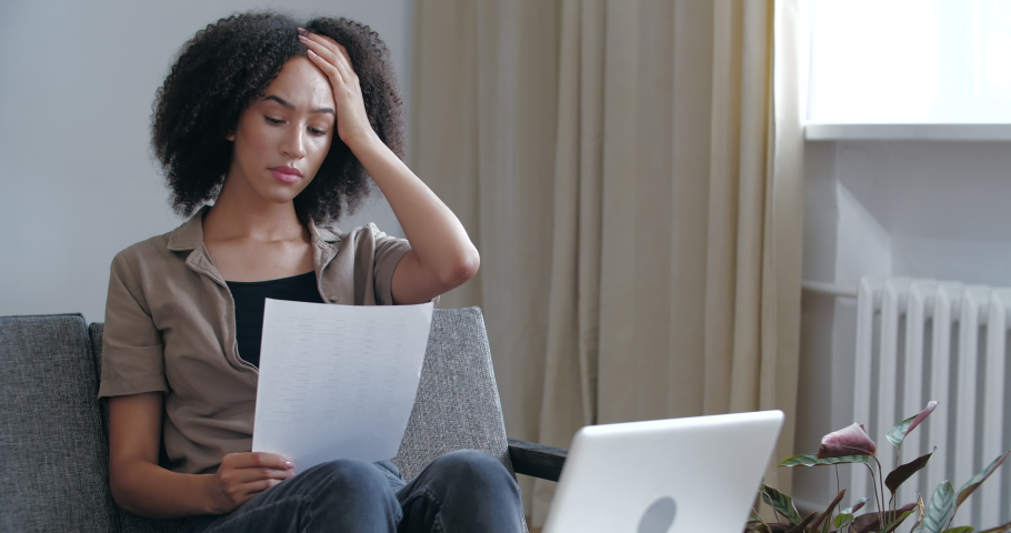 Young woried curly African girl receives letter in mail with bad news, medical tests, learns about failed exams, holds refusal notice in her hands, feels sad displeasure resentment, upset female face Royalty-Free Stock Footage #1057543843