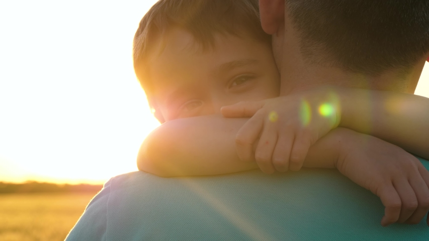 A happy child embraces his father. Portrait of a happy child. Family in the sun at sunset. Education, care. Royalty-Free Stock Footage #1057544563