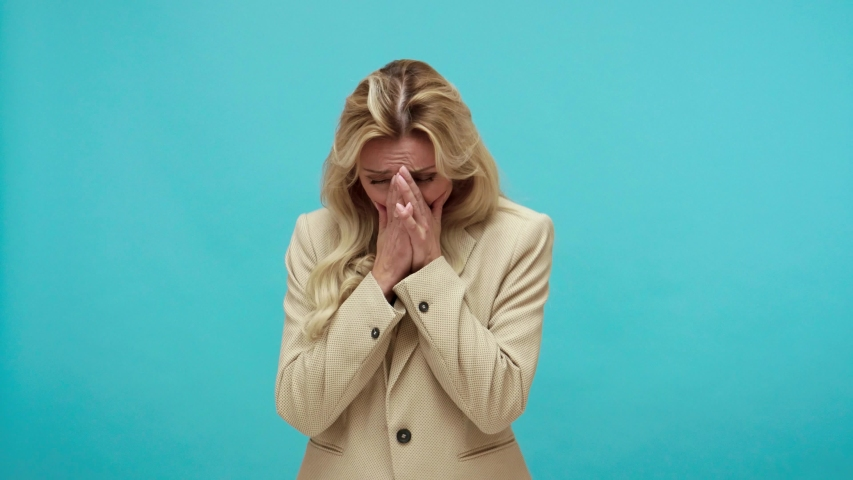 Deeply upset frustrated adult blond woman in business style jacket crying hiding face in hands, sorrow, lost of beloved, troubles. Indoor studio shot isolated on blue background
