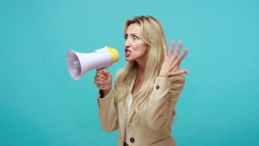 Profile portrait of nervous adult woman with blond hair loudly screaming holding speaker in hand, strict boss yelling, gender equality problem. Indoor studio shot isolated on blue background