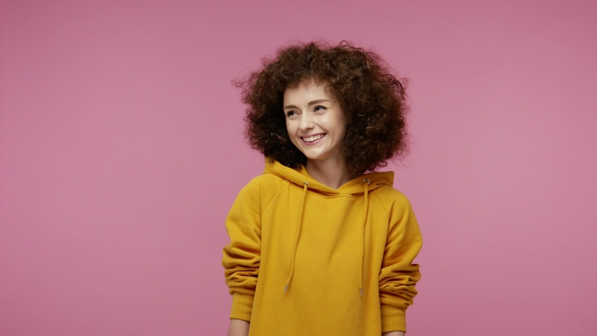 Happy joyful  young woman afro hairstyle in hoodie laughing out loud after hearing ridiculous anecdote, funny joke, feeling carefree amused, positive lifestyle. indoor isolated on pink background Royalty-Free Stock Footage #1057547134
