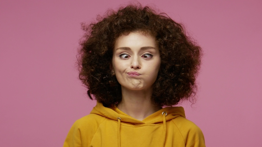 Funny amusing young funny woman in hoodie looking awkward with crossed eyes and puffed cheeks, fooling around making stupid brainless dumb expression. indoor studio shot isolated on pink background Royalty-Free Stock Footage #1057547140