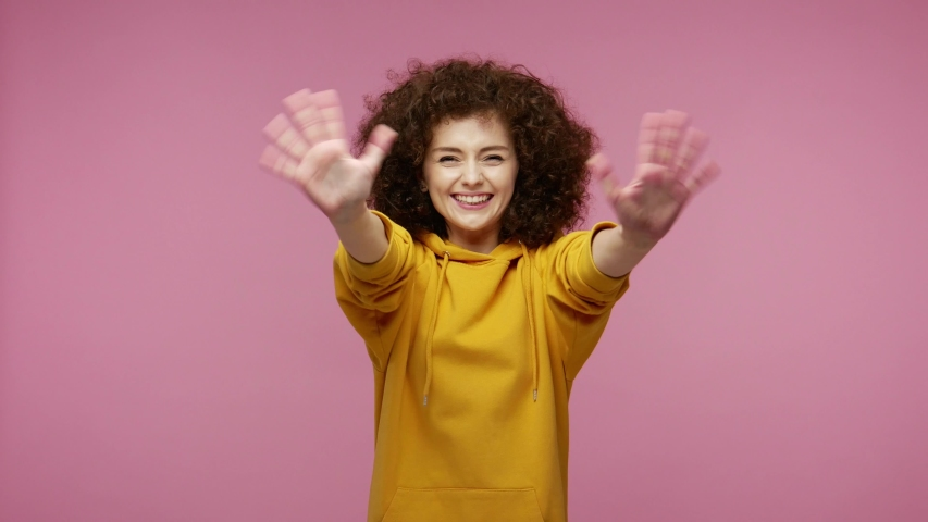 Sociable happy  young woman afro hairstyle in hoodie smiling friendly at camera and waving hands gesturing hello or goodbye, welcoming with hospitable expression. indoor isolated on pink background Royalty-Free Stock Footage #1057547146