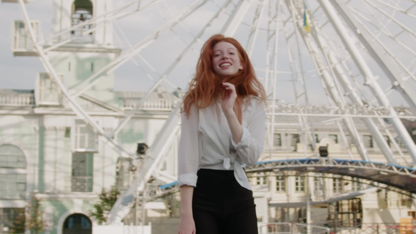 Satisfied beautiful ginger woman dances exscitedly in wonderful big city near ferris wheel. Amusement park. Attractive females. Carefree lifestyle. Freedom concept.