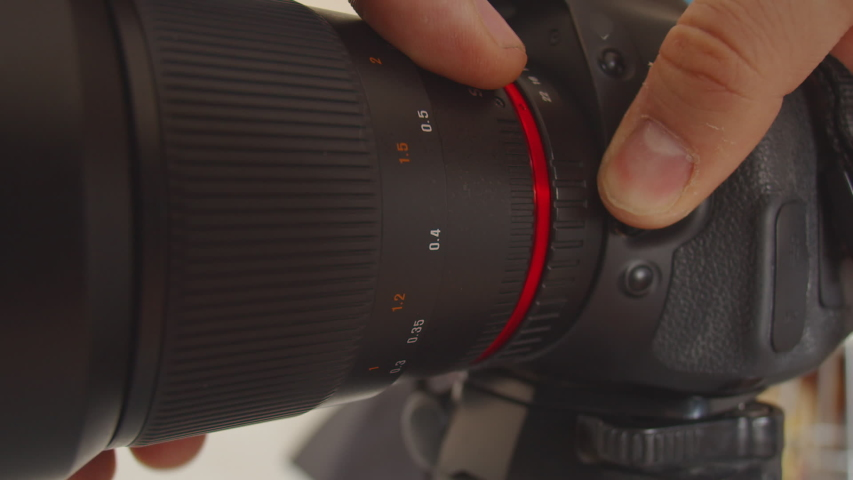 The lens is detached from the camera mount. A man's hand presses the lens mount button and detaches the lens from the camera. Close-up of disconnecting lens from the camera Royalty-Free Stock Footage #1057562206