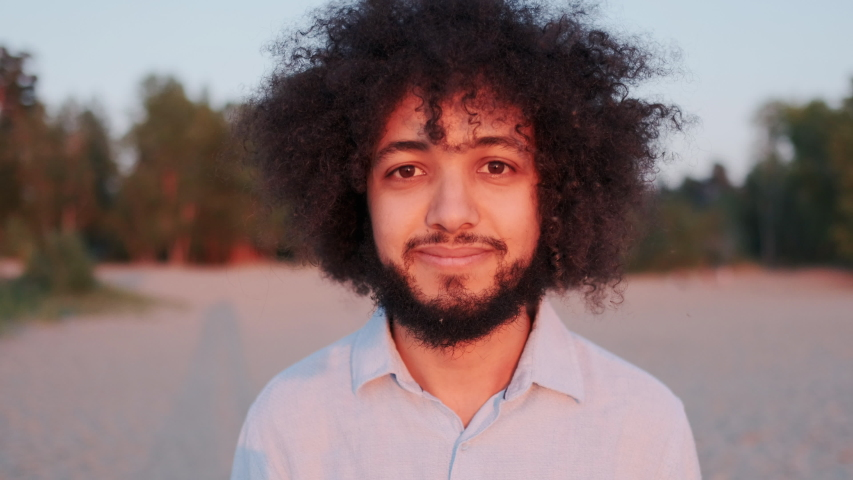 Close-up Portrait of Joyful Young Hispanic Man Curly Hair, Standing Alone in Park, Smiling and Looking at Camera. Stylish Authentic People, Expressive Charismatic Independent Person.