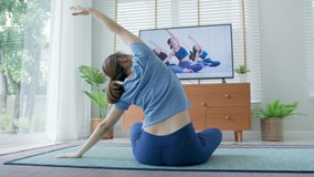 Back view : asian woman stretching body and yoga in living room at home with pet, watching live or video tutorial TV online. Activity during quarantine and social distance new normal concept.