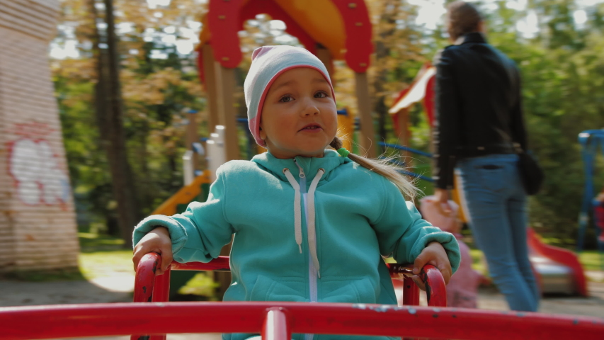Portrait of cute little girl having fun on merry-go-round, she smiles and happy. A handsome emotional kid rides on carousel at children playground in park, real emotions. Royalty-Free Stock Footage #1057570969