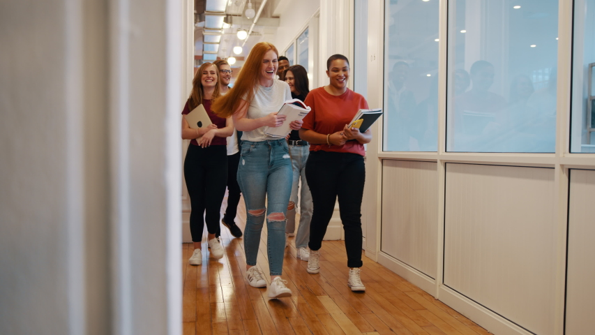 Group of university students going for lecture. Smiling girls and boys with books walking through college corridor.  Royalty-Free Stock Footage #1057573738