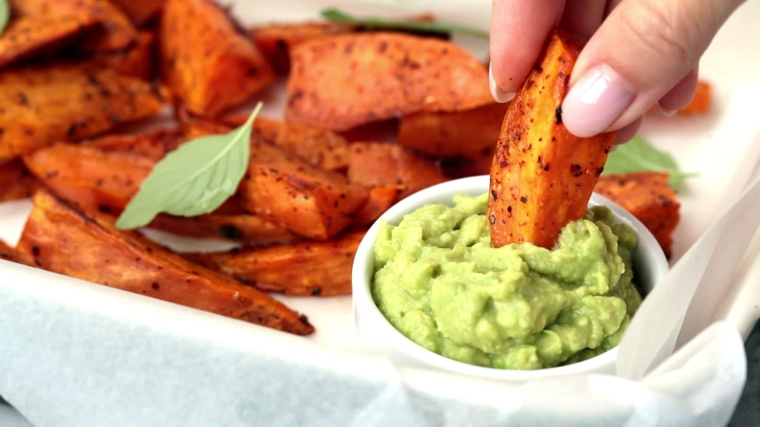 Baked sweet potato wedges with guacamole. Healthy vegan food concept. | Shutterstock HD Video #1057577809