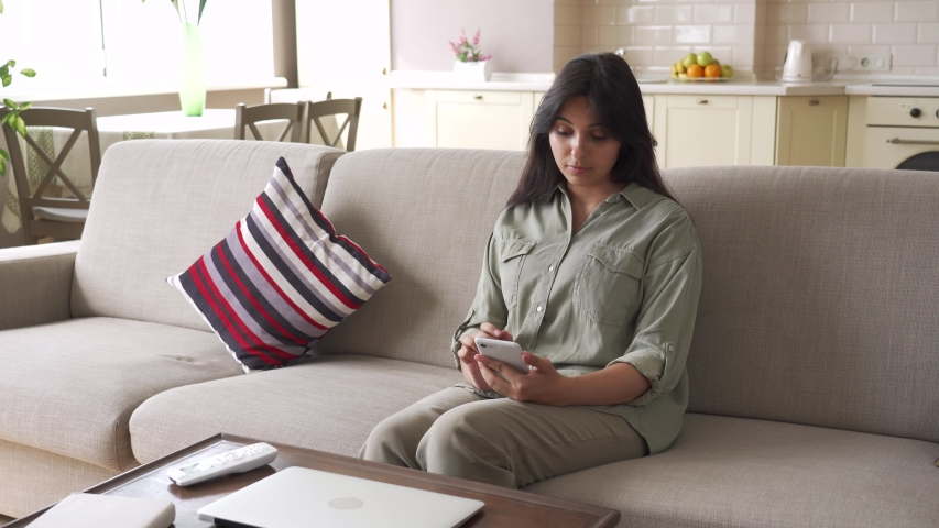 Happy indian woman feels hot using remote control switching air conditioner split appliance system at home sitting on sofa. Smiling indian lady enjoying comfort and fresh cold cool air in living room.