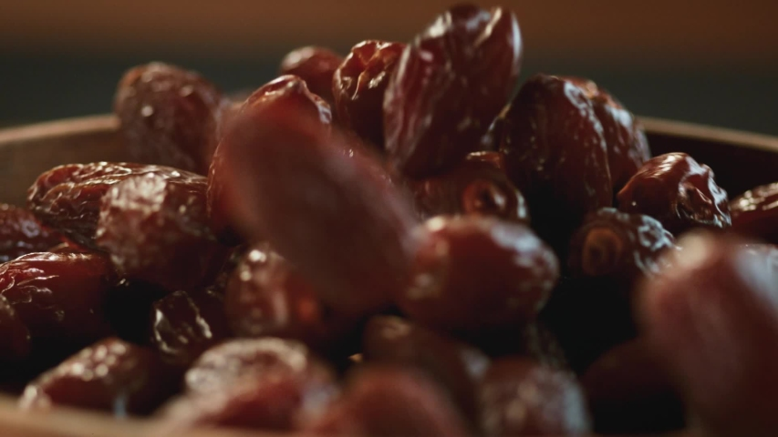 Very Close-up.In a beautiful light, dried date fruit fall into the wooden plate in slow motion. Macro,Phantom Camera,900 fps video. Royalty-Free Stock Footage #1057582282