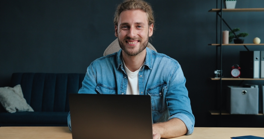 Young Successful Freelancer is sitting at Home Office, smiling at the Camera. Portrait of Satisfied Young Man is working on his Laptop at Home, looking directly in Shoot. Casual Style. Freelance. Royalty-Free Stock Footage #1057584694
