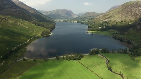Aerial fiew flying towards a beautiful lake in a deep valley (Buttermere, Lake District, Cumbria)