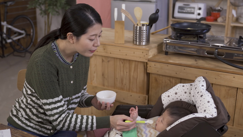 asian woman giving her young child some porridge and saying ah while feeding.