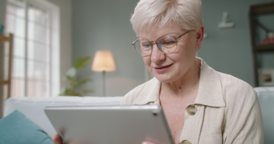 Senior caucasian lady having video chat with relatives or consulting with doctor during self-isolation, using tablet computer at home 4k footage