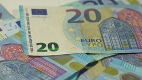 Closeup view video footage of several banknotes of paper Euro money isolated on white wooden table background. Person counts blue 20 paper banknotes of euros money.