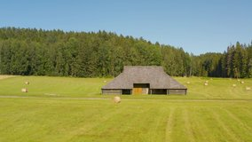 Clip of old countryside barn in green field during summer day. Wooden building