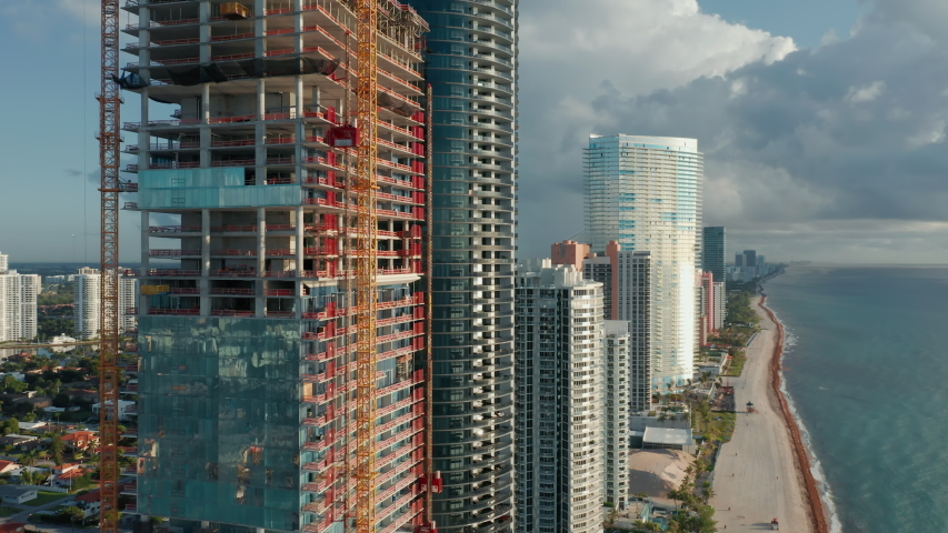 4K aerial view on building construction with beautiful ocean view. Construction of prestige waterfront skyscraper from blue glass and concrete. Construction business in Miami, Sunny Isles Beach, USA Royalty-Free Stock Footage #1057599010
