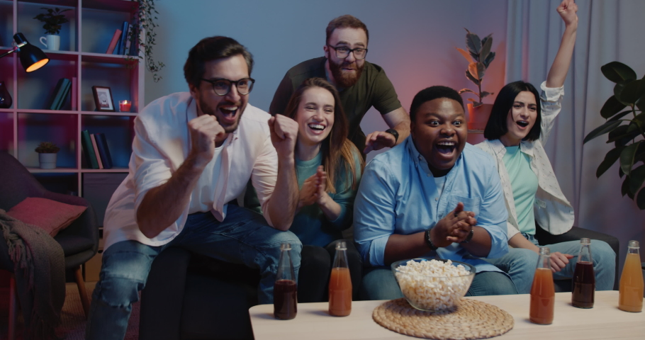 Young sport fans getting together and watching start of Olympic Games. Cheerful friends sitting near TV with drinks and popcorn bowl. Concept of sport and entertainment. Home background. Royalty-Free Stock Footage #1057602892