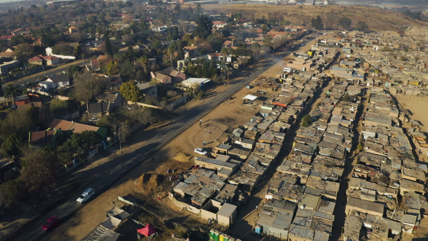 Inequality.Aerial fly over view of an informal settlement Kya Sands squatter camp right next to middle class suburban housing, Gauteng Province, South Africa