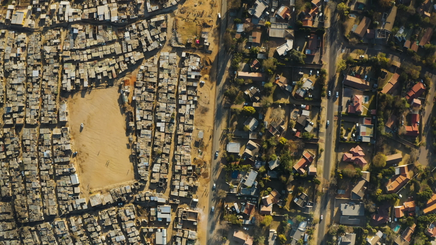 Inequality.Poverty.Aerial straight down view of an informal settlement Kya Sands squatter camp right next to middle class suburban housing, Gauteng Province, South Africa Royalty-Free Stock Footage #1057609936