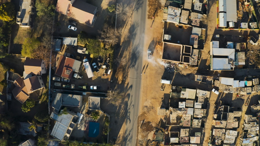 Poverty.Inequality.Aerial close-up straight down view of an informal settlement Kya Sands squatter camp right next to middle class suburban housing, Gauteng Province, South Africa
