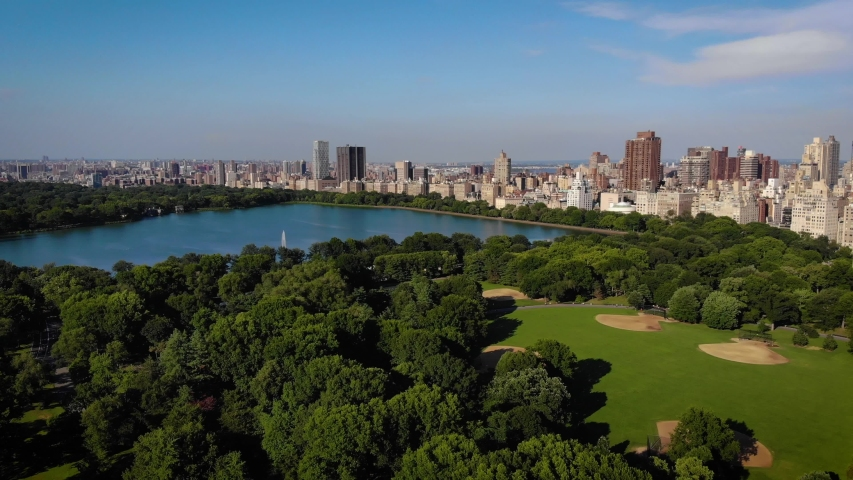 Drone flying above Central Park in New York USA during summer time. Manhattan buildings river green grass trees nature baseball fields playground blue sky good weather