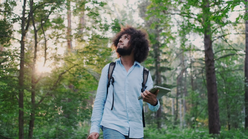 Young Curly Male Inspirational Environmentalist Walking in Forest. Nature Lover Hiking in Woods. Holding Tablet PC.Concept of Privacy and Isolation, Traveling Alone. Calmness, Harmony with Nature.