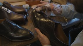 Close up shoe manufacturing workshop. Shoemaker rubs shoes with cream sews shoes. Handmade work shoes. Leather shoes.
