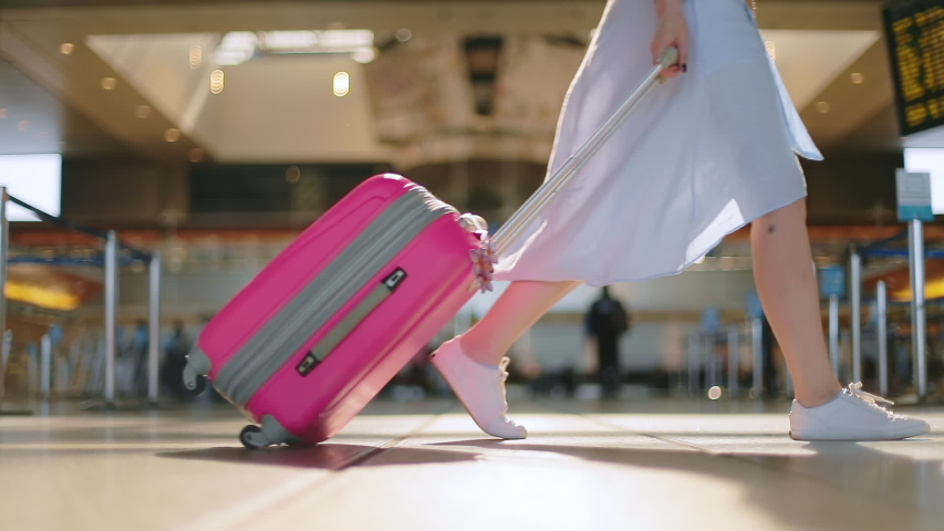 Close up view on traveler in the empty airport during Coronavirus outbreak. Slow motion of woman legs in white shoes and blue dress carrying her pink travel luggage on the wheels. Safe travels, USA