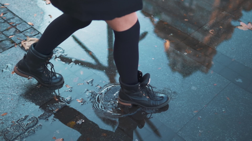 Woman having fun splasing water at rainy wet weather. female feet walking on city street pool or puddle in waterproof shoes. Playful carefree woman enjoying urban spring in rubber boots. Concept of joy Royalty-Free Stock Footage #1057621924