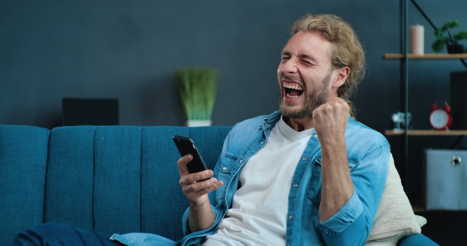 Portrait of happy businessman enjoying Success on Mobile Phone at home office. Closeup joyful Guy reading good news on Phone in slow motion. Surprised Man celebrating Victory on phone in Apartment.