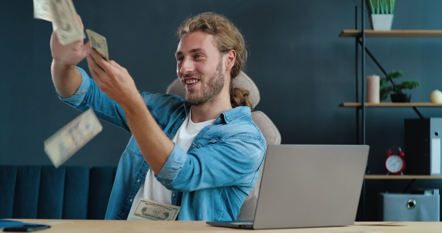 Young Startup Businessman scatters the Dollars funny in Office. Young IT-tech worker making Money rain, making Money Online. Having Success in World Economic. Technology. Distant Job. Finance. | Shutterstock HD Video #1057627738