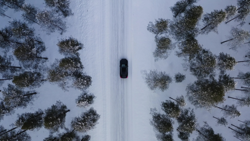 Aerial top view from drone of suv vehicle driving on snowy ice road exploring local landscapes in winter, bird's eye view of automobile car moving on area surrounded by beautiful coniferous forest  Royalty-Free Stock Footage #1057628311