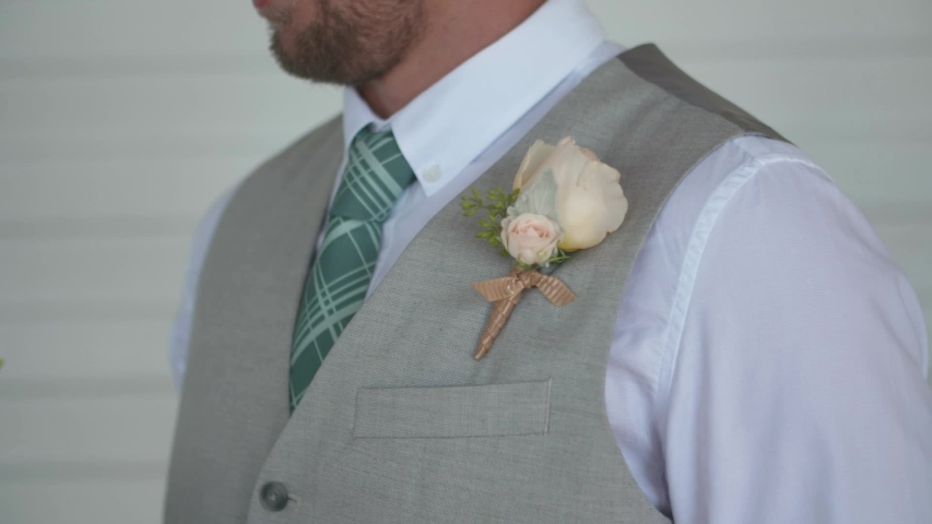 Caucasian Groom gets white rose Boutonniere pinned by woman on grey suit. Close up shot