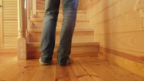 Person walking up of wooden indoor stairs at home in a low angle view