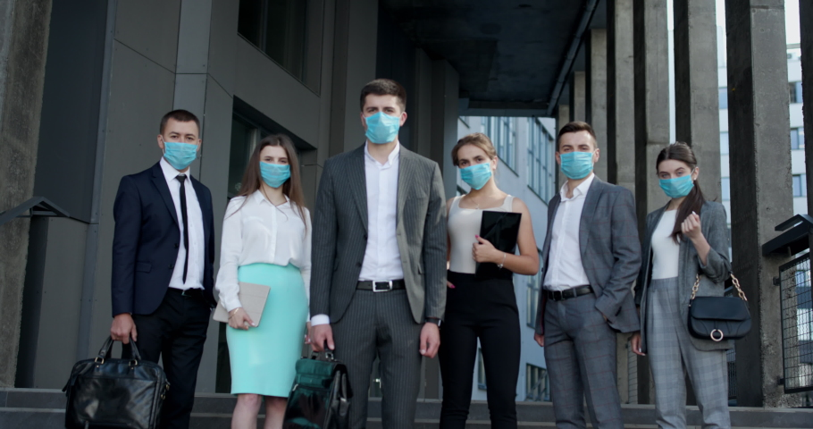 Corporate team portrait in Protective Mask. Professional business people in Protective Mask look at camera standing outside business center. Royalty-Free Stock Footage #1057630255