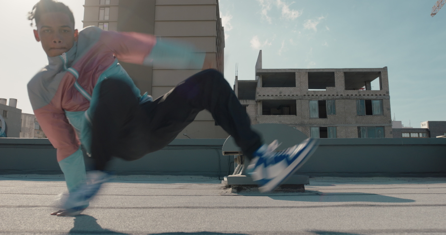 Dancing man breakdancing on roof top hip hop dancer practicing dance routine performing freestyle moves in city | Shutterstock HD Video #1057631677