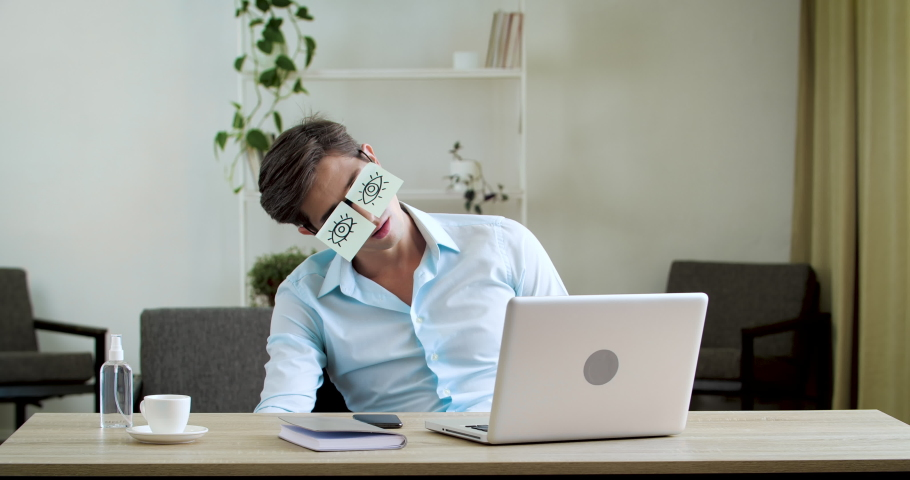 Tired comic male man manager pretends working sleeping with stickers on face sitting at desk laptop. Funny lazy office businessman student napping at workplace covering eyes with sticky notes glasses Royalty-Free Stock Footage #1057635373