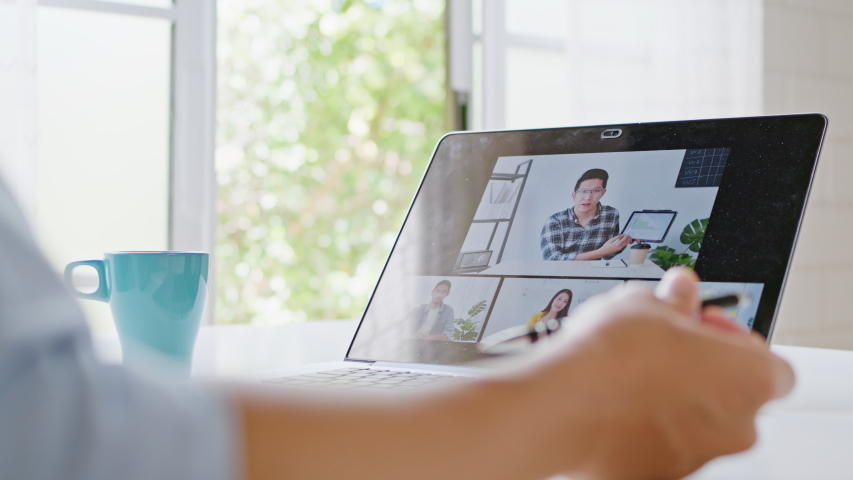 Asian man video call conference, online remote meeting with business coworker, at home. New normal lifestyle, social distancing, internet technology, businessman work from home concept. Slow motion Royalty-Free Stock Footage #1057637488