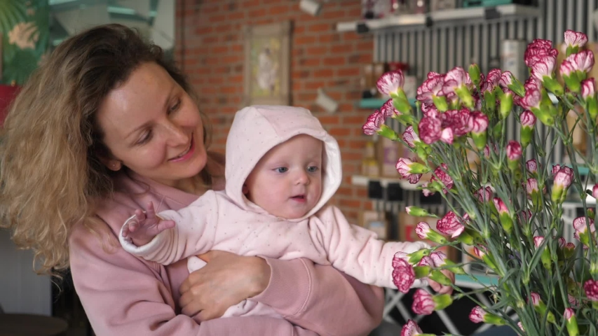 Beautiful young mother showing pink flowers to her baby daughter indoors.