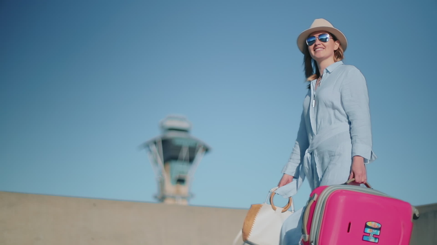 Slow motion pretty stylish travel walking outdoor with airport dispatcher tower on motion background. Smiling woman traveling with pink suitcase, USA. Beautiful woman walking in the airport at sunset