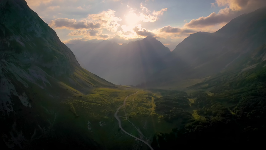 Alps Mountain Aerial sun rays emerging though the dark storm clouds in the mountains.Mountain Range Silhouette Sunrise Aerial View. Scenic Dawn Sunlight Mountainous Cottage Village Overview.  | Shutterstock HD Video #1057656808