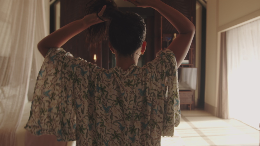 Rear view of a woman tying her hair and walking into the hotel bathroom and taking off her clothes. Woman going in bathroom for taking a bath in hotel.  Royalty-Free Stock Footage #1057656907