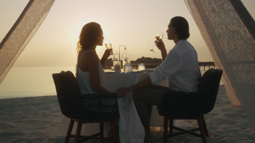 Beautiful couple on a dinner date at a beach. Couple at beach restaurant enjoying glass of wine during sunset.